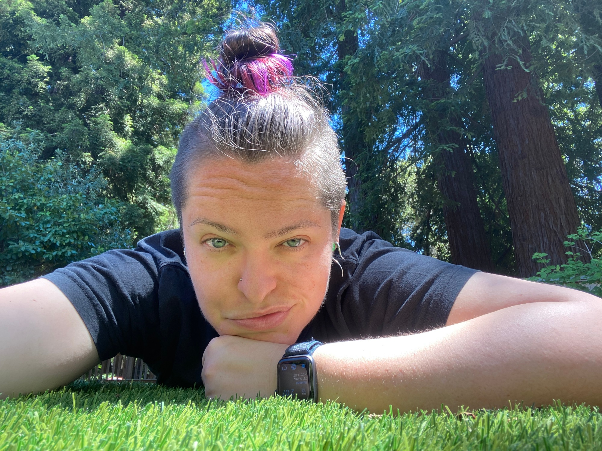 A white non-binary person lays on grass and looks directly into the camera.